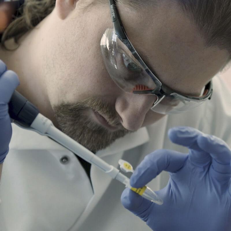 Image: Lab technician filling vial